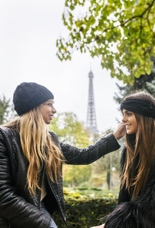 France, Paris, two best friends sitting in a park with the Eiffel Tower in the background - MGOF03091
