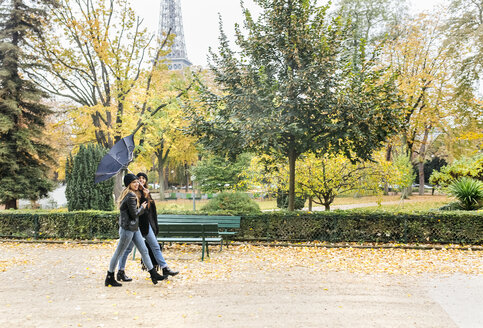France, Paris, two young women walking in park with the Eiffel Tower in the background - MGOF03094