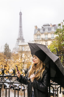 France, Paris, young woman using her smartphone with the Eiffel Tower in the background - MGOF03097