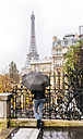 France, Paris, woman under umbrella with the Eiffel Tower in the background - MGOF03100