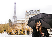France, Paris, young woman talking on cell phone under umbrella with the Eiffel Tower in the background - MGOF03103