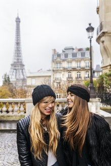 France, Paris, two best friends walking down the street with the Eiffel Tower in the background - MGOF03106
