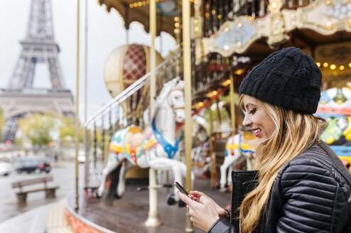 France, Paris, young woman using her smartphone with a carousel and the Eiffel Tower in the background - MGOF03109