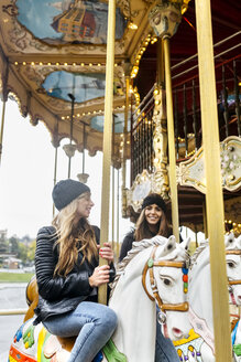 France, Paris, two best friends riding a carousel - MGOF03112
