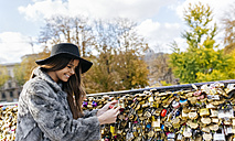 France, Paris, young woman putting a love lock on a bridge over the Seine River - MGOF03115