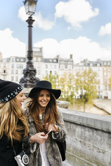 France, Paris, two happy female tourists walking in the city - MGOF03118