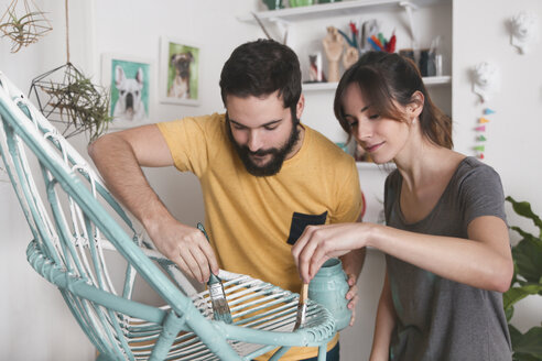 Young couple painting wicker armchair at home - RTBF00775