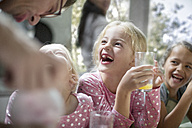 Father giving orange juice to happy girls at home - ZEF13212