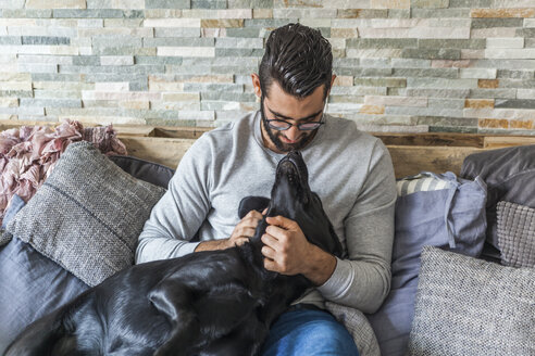 Man cuddling with his dog on the couch at home - TCF05320