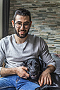 Portrait of smiling young man with his dog at home - TCF05326