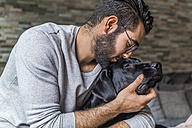 Man cuddling with his dog at home - TCF05329