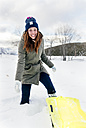 Portrait of young woman having fun with sled in the snow - MGOF03131
