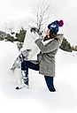 Young woman playing with her border collie in the snow - MGOF03137
