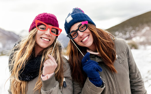 Two young women with fake glasses having fun in the snowy mountains - MGOF03155