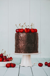 Cake with chocolate icing and cherries on top on cake stand - RTBF00784