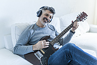Mature man at home playing electric guitar and wearing headphones - TCF05334