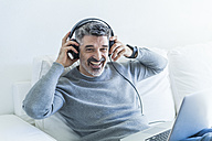 Portrait of happy mature man at home using laptop and wearing headphones - TCF05337