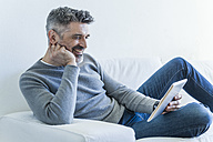 Smiling mature man at home using tablet - TCF05340