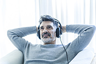 Relaxed mature man at home wearing headphones - TCF05346