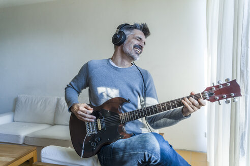 Mature man at home playing electric guitar and wearing headphones - TCF05349