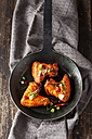 Three marinated and grilled chicken wings in cast-iron frying pan - CSF28209