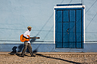 Cuba, man with guitar walking on the street - MAUF01035