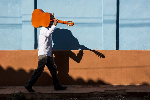 Cuba, man with guitar walking on the street - MAUF01038