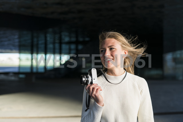 Portrait of smiling woman with camera - KKAF00540