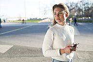 Portrait of woman with cell phone looking at distance - KKAF00543