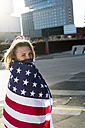 Spain, Barcelona, portrait of young woman wrapped in US American flag - KKAF00549