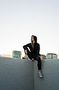 Spain, young woman dressed in black sitting on a wall looking at distance - KKAF00567