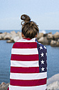 Back view of young woman standing in front of the sea wrapped in US American flag - KKAF00579