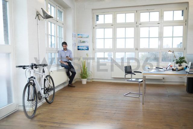 Man using cell phone in a modern informal office - FKF02196