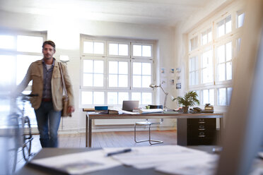 Man with bicycle in a modern informal office - FKF02202