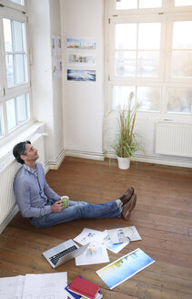 Man sitting on the floor in office - FKF02214