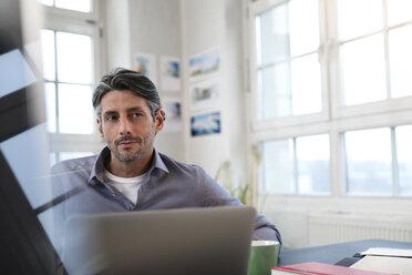 Man at desk in office thinking - FKF02217