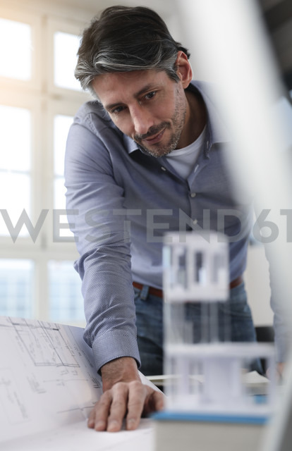 Man in office looking at architectural model - FKF02220