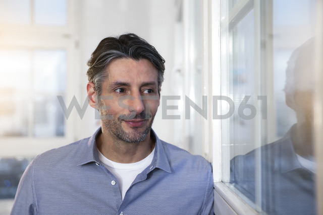 Smiling man in office looking out of window - FKF02226