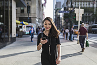 USA, New York City, Manhattan, portrait of smiling young woman dressed in black looking at cell phone - GIOF02484