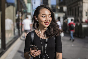 USA, New York City, Manhattan, young woman listening music with cell phone and earphones on the street - GIOF02490