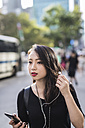 Portrait of young woman with   earphones and cell phone watching something - GIOF02493