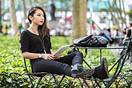 USA, New York, young woman with tablet sitting at city park - GIOF02499