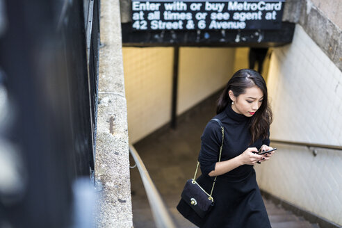 USA, New York City, Manhattan, young woman dressed in black walking upstairs text messaging - GIOF02505