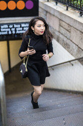 USA, New York City, Manhattan, young woman dressed in black walking upstairs - GIOF02508