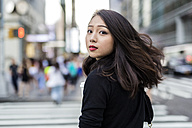 USA, New York City, Manhattan, portrait of young woman looking over her shoulder while crossing street - GIOF02514
