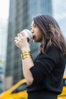 USA, New York City, Manhattan, young woman drinking coffee to go on the street - GIOF02517