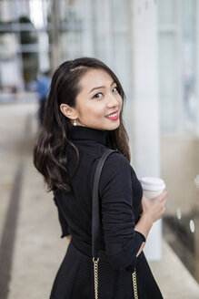 Portrait of smiling young woman with coffee to go looking over her shoulder - GIOF02520
