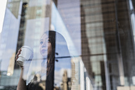 USA, New York City, Manhattan, young woman with coffee to go behind glass pane - GIOF02523