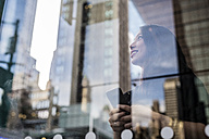 USA, New York City, Manhattan, smiling young woman behind glass pane looking up - GIOF02526