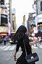 USA, New York City, Manhattan, back view of woman with coffee to go on  the street - GIOF02532